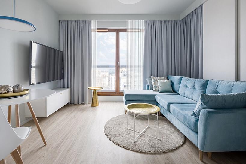mały salon zjasną drewnianą podłogą zdługą niebieską sofą na tle szarych zasłon