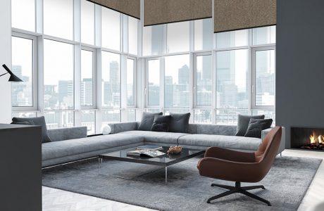 duży salon z dużą narożną sofą na tle ściany z okien z wysokimi brązowymi roletami