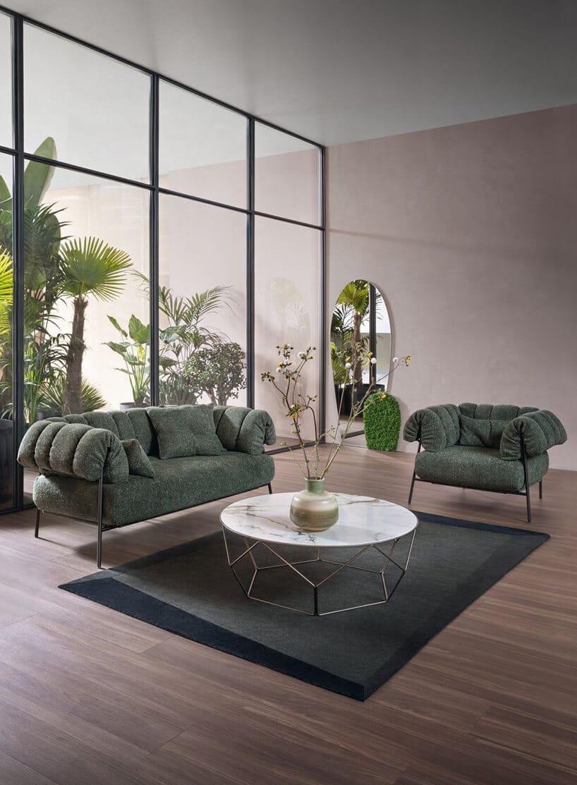 dwie ciemno zielone małe kanapy wdużym pomieszczeniu zprzeszkleniem