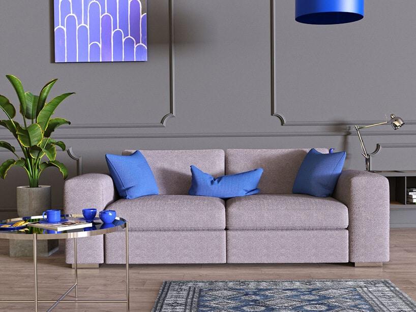 szara komoda przy ścianie zdekorami zfiletowym obrazem obok niebieskiego klosza lampy