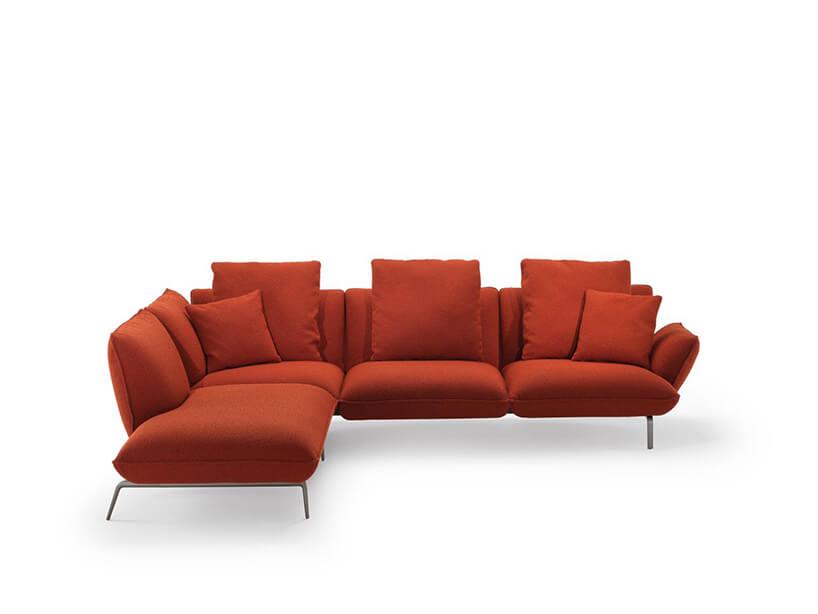 czerwona kanapa rogowa zpoduszkami na chromowanych nóżkach