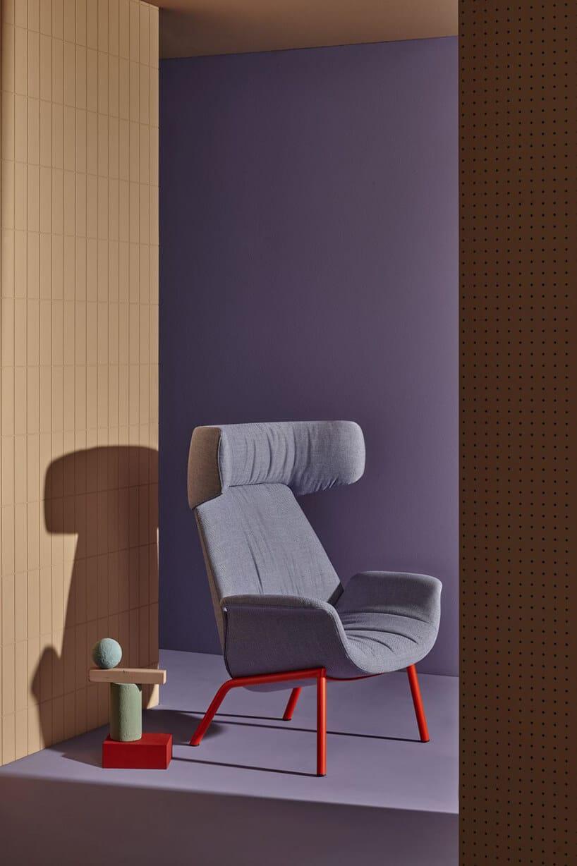szary fotel zczerwoną ramą wprzejściu zbeżową oraz fioletową ścianą