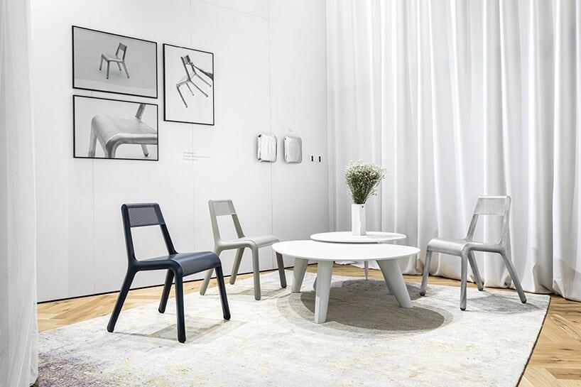 szaro białe wnętrze zkrzesłami wczerni ibieli przy niskim stoliku wbiałym kolorze