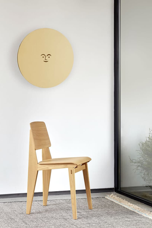 drewniane krzesło przy białej ścianie zokrągłym panelem zdrewna