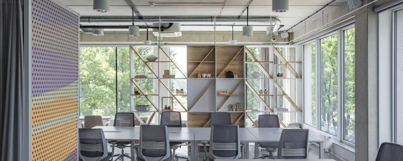 przestrzeń biurowa wConcordia Design szare biurka ikrzesła na tle mebli zdrewnianych