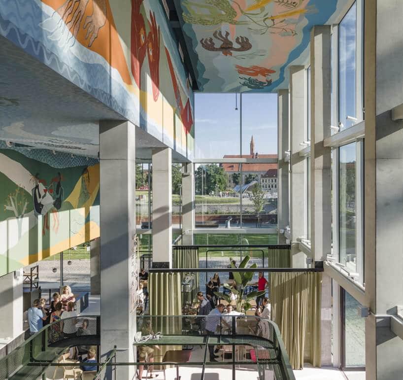 przestrzeń wspólna wConcordia Design na tle przeszklonych ścian ikolorowych rysunkach pod sufitem