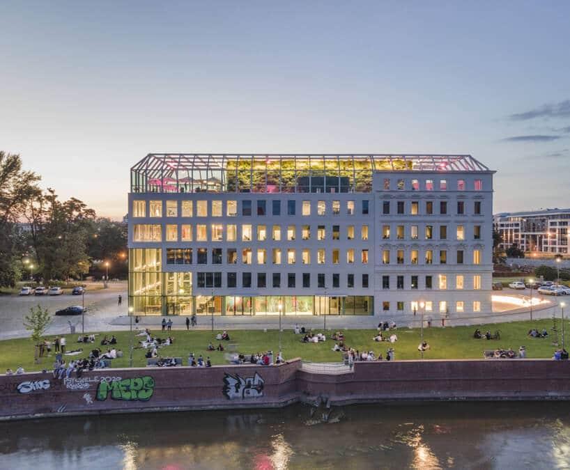 budynek Concordia Design nowoczesna biała elewacja zprzeszklonym dachem wieczorem