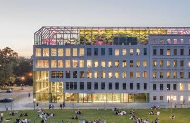 budynek Concordia Design nowoczesna biała elewacja z przeszklonym dachem wieczorem