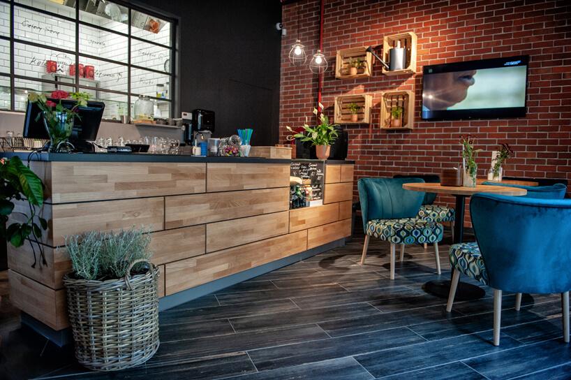 przestrzeń kuchenna wbiurze obok stolików zkrzesłami od Consido