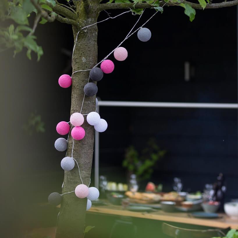 sznur zoświetleniem cotton balls wokół drzewa wogrodzie