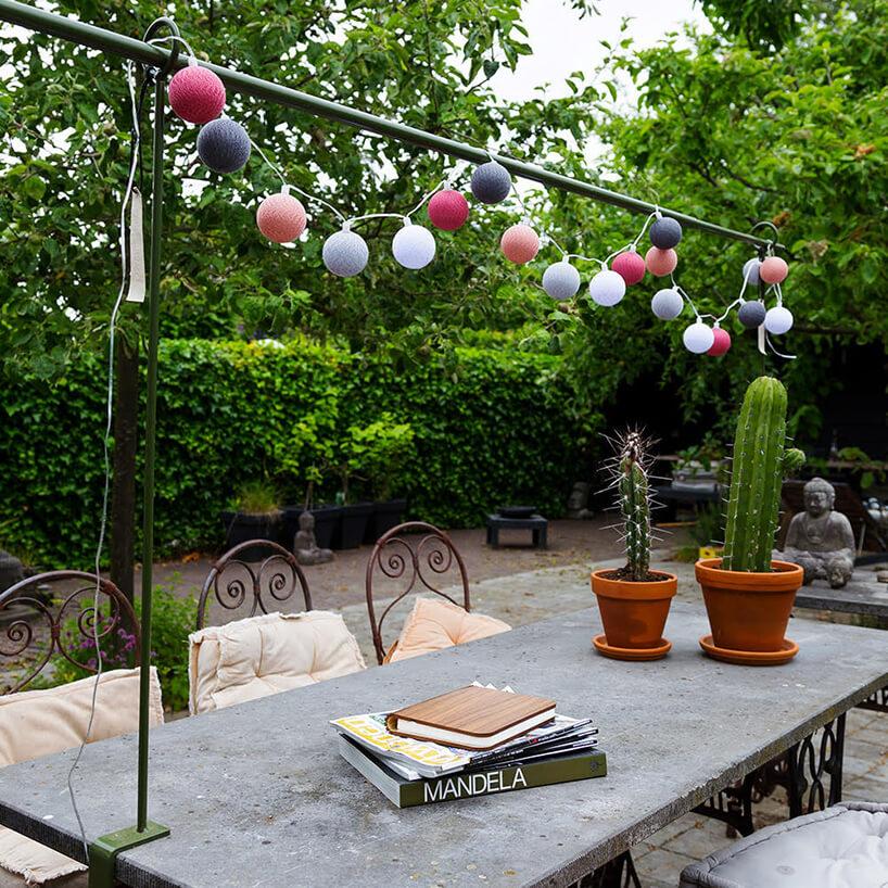 duży stół na tarasie zkaktusami na blacie icotton balls ponad stołem
