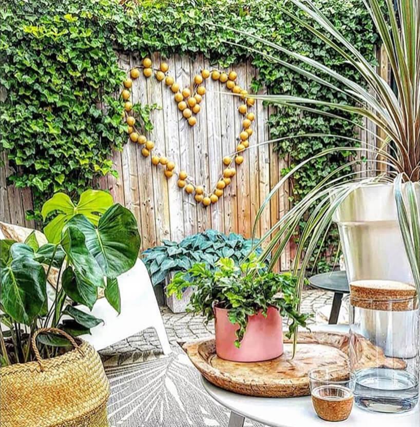 mały taras ogrodzony wysokim płotem zdużym sercem zcotton balls