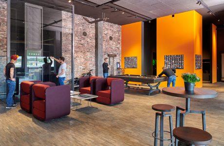 nowoczesne wnętrze biurowe z nowoczesnymi czerwono fioletowymi fotelami od VANK na tle ceglanej ściany obok stołu do bilardu