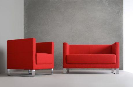 czerwona sofa i czerwony fotel na tle szarej ściany i podłogi