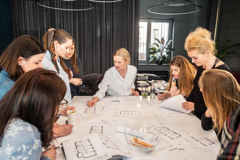 siedem kobiet przy stole podczas oceny projektów