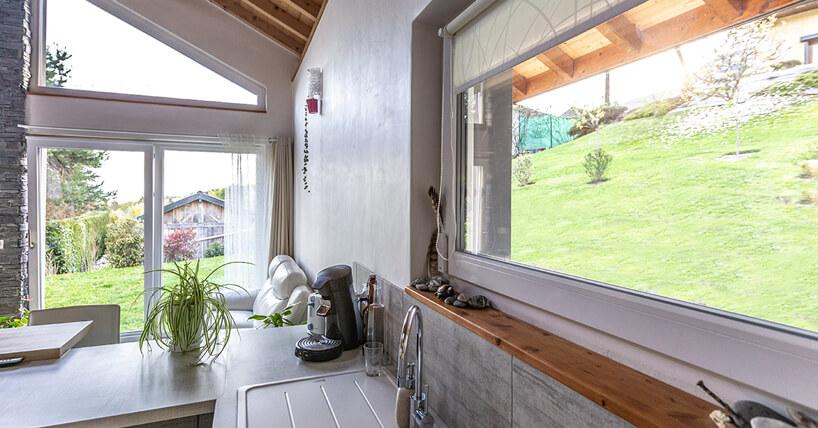 okno wdużej kuchni zdrewnianym parapetem idekoracjom zkamienii