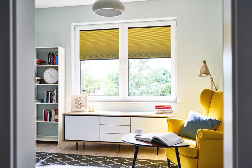 żółte rolety wmałym salonie zżółtym fotelem