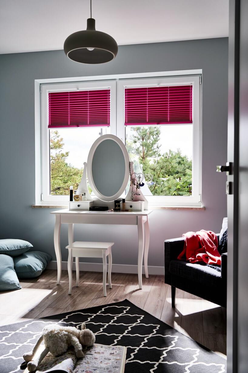 biała toaletka zowalnym lustrem na tle czerwonych żaluzji okiennych