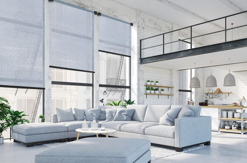niebieskie meble wsalonie loftu iduże rolety okienne