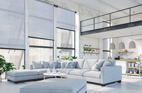 niebieskie meble w salonie loftu i duże rolety okienne