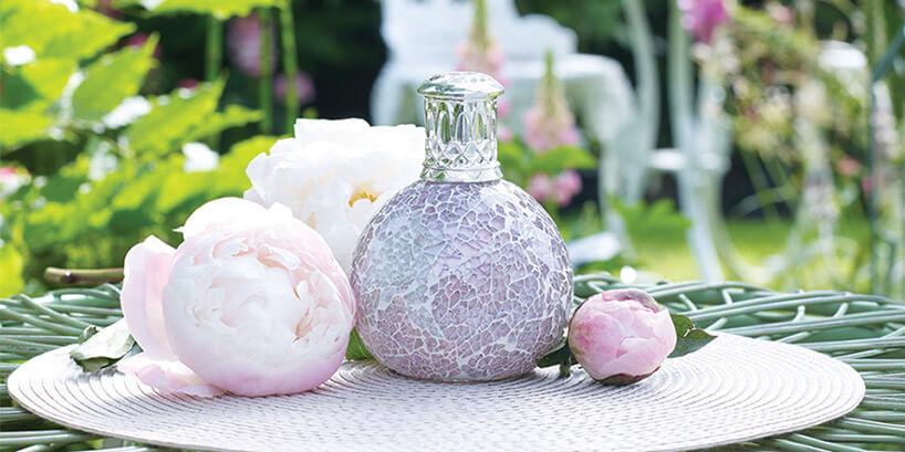 lampa zapachowa zmozaikową powierzchnią na stoliku obok kwiatów