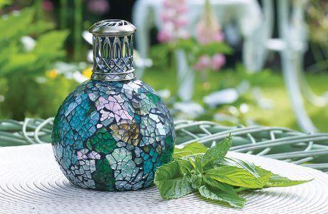 zielono-niebieska lampa zapachowa na stoliku obok kwiatów