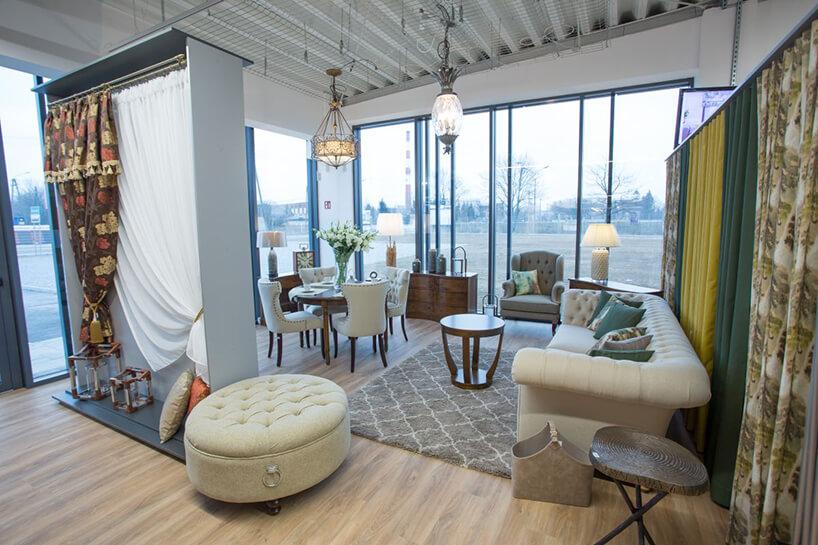 elegancki showroom zdużą plisowaną sofą przy małym drewnianym stoliku na tle szarego fotela