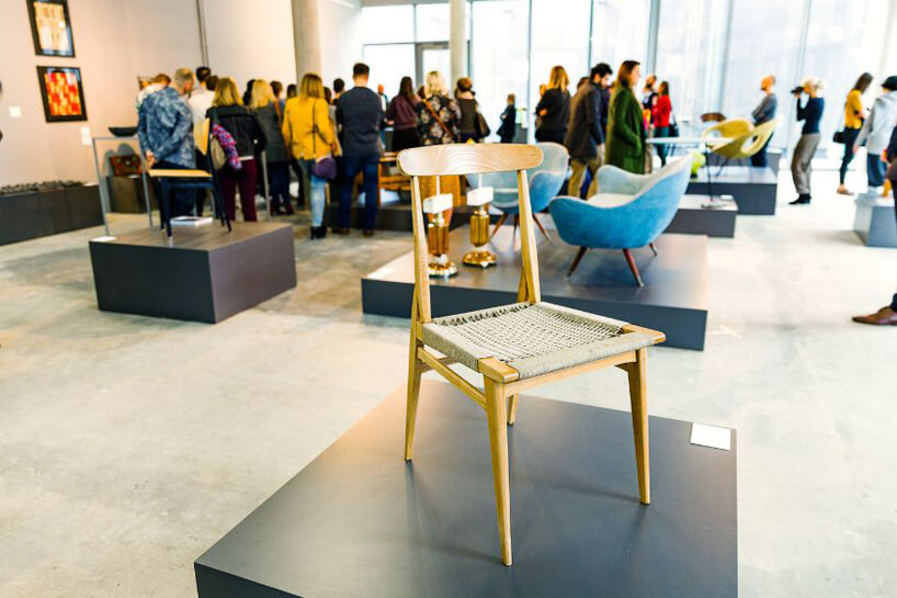 drewniane krzesło zplecionym siedziskiem na szarym podium