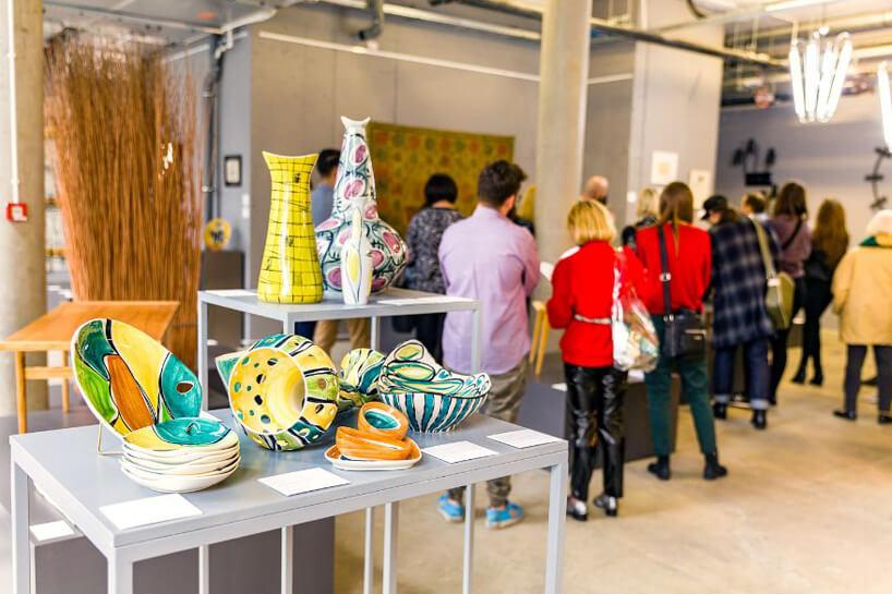 wzorzyste ceramiczne naczynia na tle odwiedzających ekspozycje