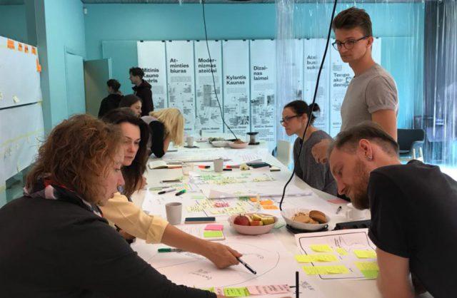 klika młodych osób siedzących przy stole i wspólnie pracujących