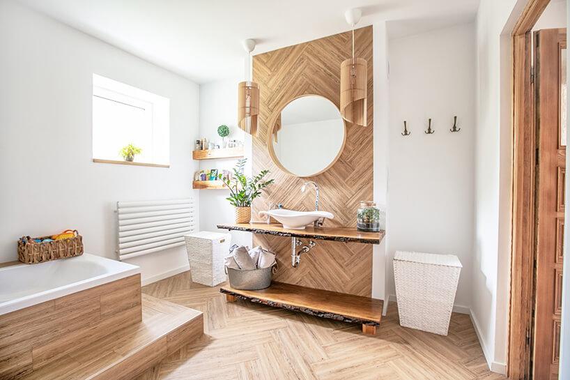 elegancka białą łazienka od Koło zdrewnianą zabudową lustra zumywalką oraz wanną