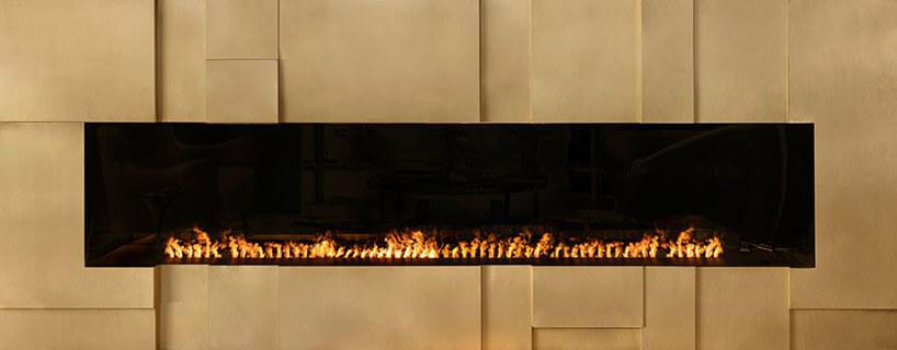 kominek ze złotymi elementami imałym płomieniem wśrodku