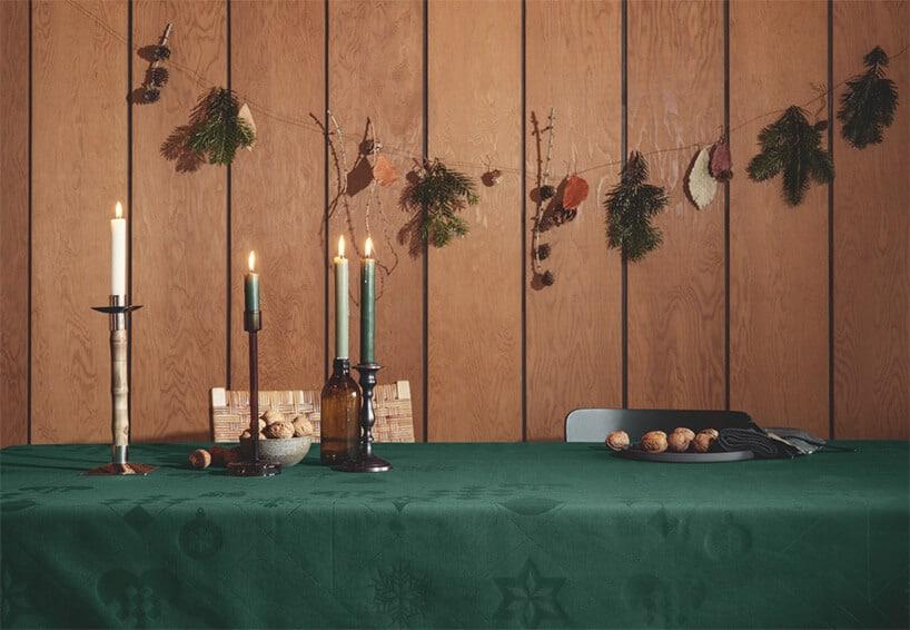 zielony stół ze świeczkami przy ścianie zdesek zozdobami światecznymi