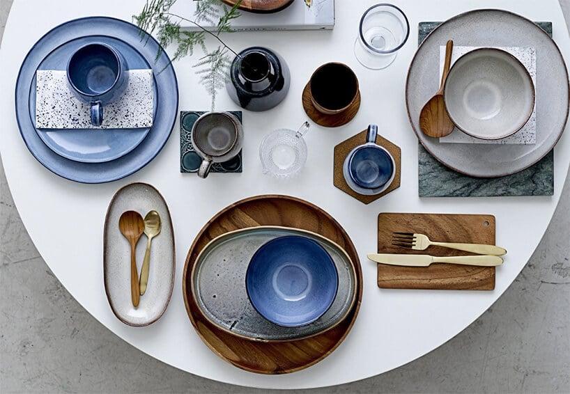 biały stół zniebieskim talerzami oraz dodatkami drewnianymi