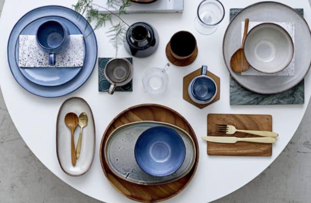 biały stół z niebieskim talerzami oraz dodatkami drewnianymi
