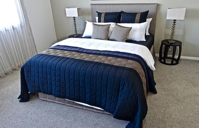 duże srebrne łóżko zniebieską narzutą ze zsrebrnymi psaiastymi poduszkami dekoracyjnymi idużymi niebieskimi pdoszukami