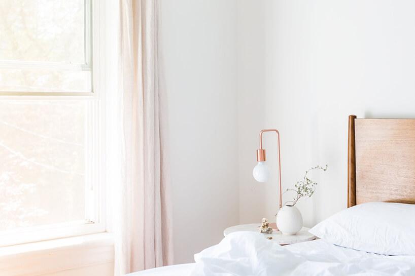 elegancka jasna zasłonka wjasnej sypialni obok okrągłego stolika zlampką bez klosza zmiedzianą podstawą imocowaniem