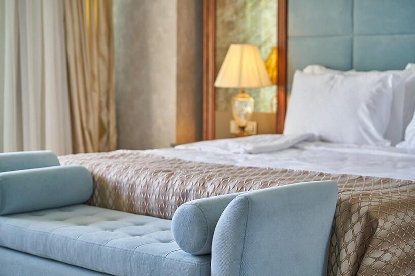 niebieska sofa bez oparcia przy dużym łóżku ze złota narzutą na dużym łóżko na tle złotych zasłon