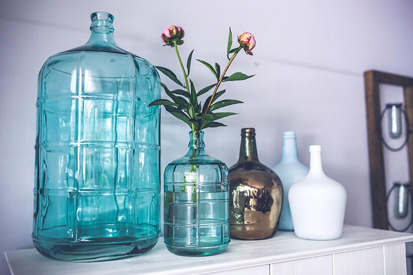 duży imały wazon wniebieskim kolorze wkształcie butelki obok trzech wazonów zwąską szyjką wbiałym izłotym błyszczącym kolorze