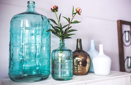 duży i mały wazon w niebieskim kolorze w kształcie butelki obok trzech wazonów z wąską szyjką w białym i złotym błyszczącym kolorze