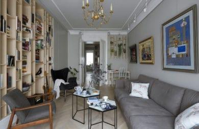 salon z ścianką drewnianą z półkami i retro meblami w kolorze szarym oraz obrazami na ścianie