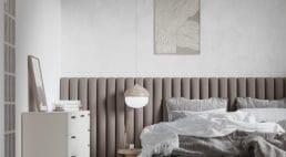 pionowy materiałowy zagłówek wkolorze brązowym przy łóżku zbiało szarą pościelą