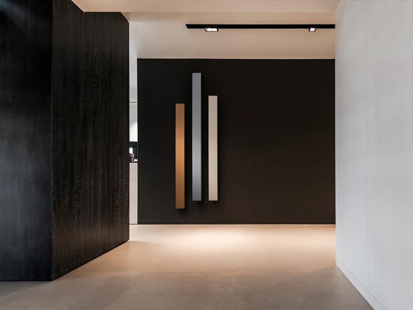 trzy pionowe grzejnik MONO BEAM od VASCO na czarnej ścianie holu