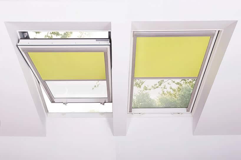 okna dachowe zżółtymi zasłonami na białym suficie ze skosem