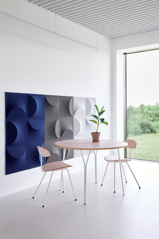 panele akustyczne zawieszone na ścianie wsalonie wkolorze szarym oraz niebieskim obo lekkich drewnianych mebli