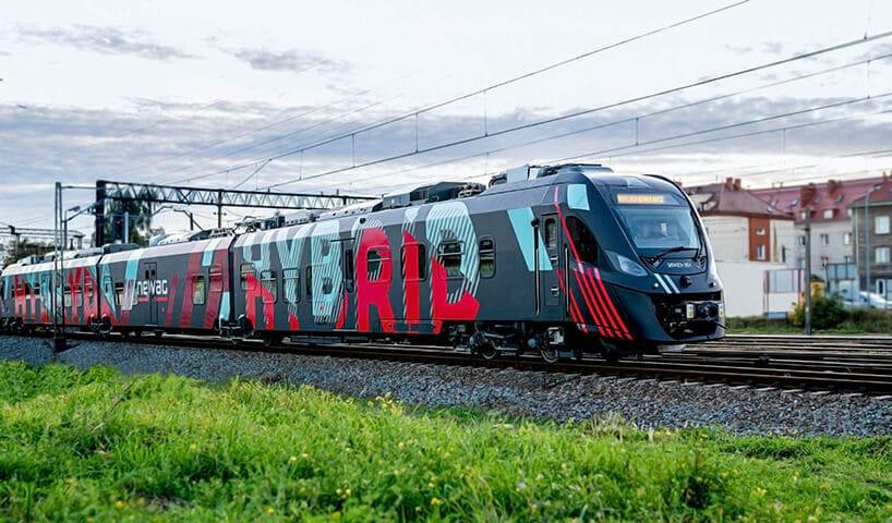 nowoczesny pociąg kolei polskiej na torach iterenie zielonym