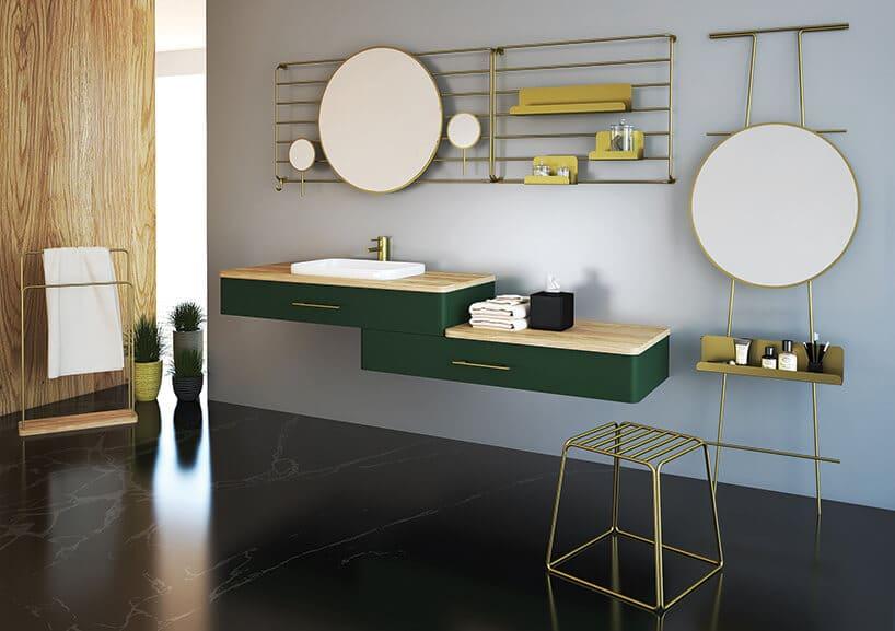 dwa okrągłe lustra na ścianie wpołączeniu zmetalową złotą konstrukcją nad umywalką na dwóch zielonych wiszących szafkach