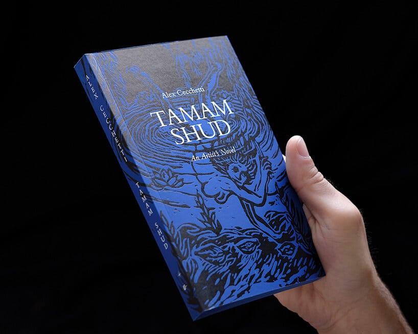 niebieska książka zczarną grafiką na okładce trzymana wręku wciemnym pomieszczeniu