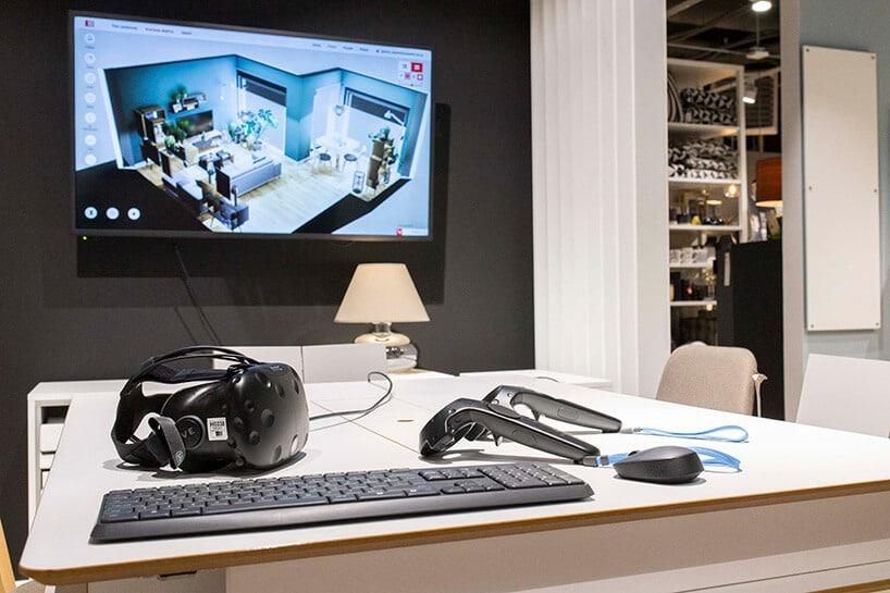 jasny stół ze sprzętem vr oraz kontrolerami na tle telewizora zwirtualnym projektem wnętrza