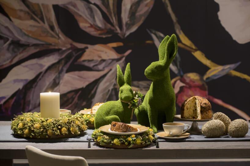 dwie zielone figurki królika na ciemnym stole